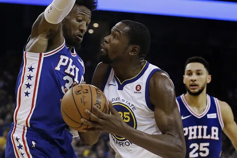 Golden State's Kevin Durant, center, drives against 76ers Robert Covington, left, as Ben Simmons watches.