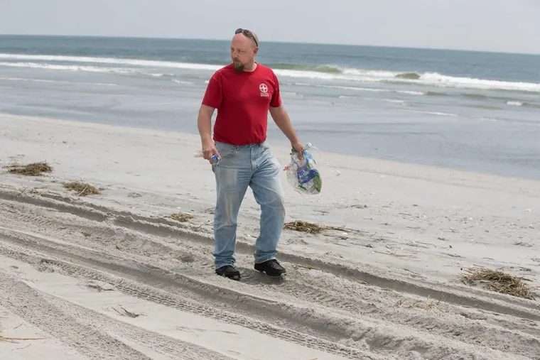 Jay Pagel, a senior field technician at the Marine Mammal Stranding Center, shown here picking up plastic on the beach, in Brigantine, New Jersey, Wednesday, May 23, 2018. JESSICA GRIFFIN / Staff Photographer