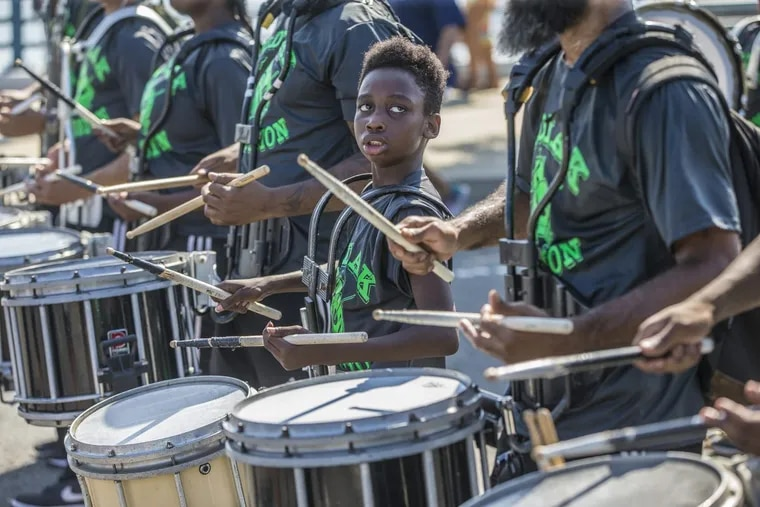 Terrell Hill, 11, of the Zodiac Percussion Drum Line, looks to one of the older drummers, as they make their way down Columbus Boulevard on September 4, 2017. A bill would have regulated drum lines in Center City.