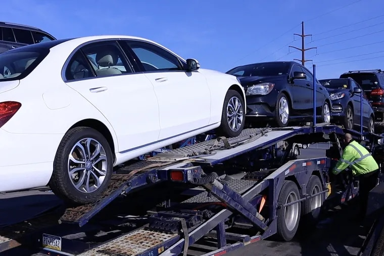 A worker loads vehicles onto a car transporter, a common sight at Manheim Auto Auction in Manheim, Pa. With a shortage of used vehicles in the post-COVID-19 economy, prices at the auction house have hit record highs.