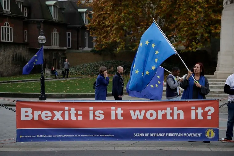 An anti-Brexit supporter holds a European flag by a banner across the street from the Houses of Parliament in London on Thursday.