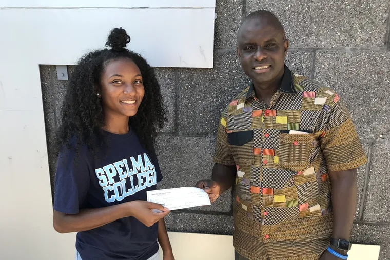Destinee Whitaker, a recent graduate of Philadelphia's George Washington Carver High School of Engineering and Science, presents a check to Joseph Sackor of the Liberian Medical Mission for water purification systems.