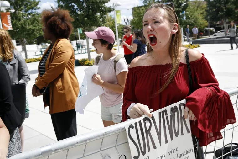 Meghan Downey, 22, a recent graduate from the College of William & Mary, reacts outside an auditorium after Education Secretary Betsy DeVos spoke about proposed changes to Title IX in September 2017.