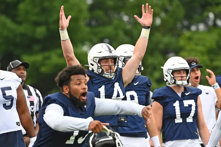 Penn State quarterback Sean Clifford (14)  and linebacker Ellis Brooks (13) react to a play during practice on Aug. 7.