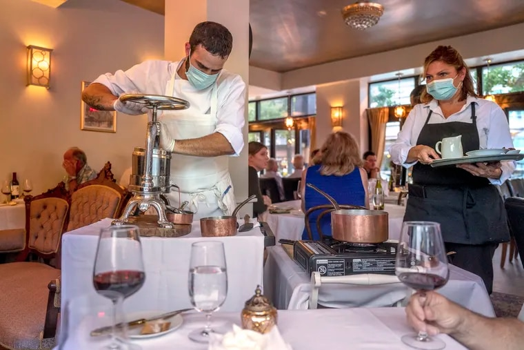 """Chef Richard """"Todd"""" Cusack turns the wheel of the his antique French duck press, pressing the duck carcass at table-side for Canard à la Presse Voyage at the new location of June BYOB in Collingswood Sept. 22, 2021, The original restaurant on East Passyunk closed due to the pandemic."""