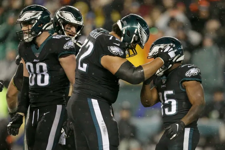 Eagles running back Boston Scott is embraced  by offensive tackle Halapoulivaati Vaitai after Scott scored against the Giants.