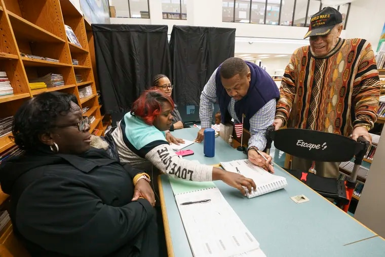 (From left) Patti Page-Walton, minority inspector; her daughter, Nichole Walton, majority inspector; and Sena Bowman, machine inspector, assist as John A. Reese III and his grandfather John A. Reese Sr. sign in to vote at the Lucien E. Blackwell West Philadelphia Regional Library last week.