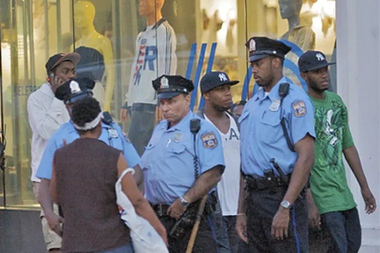 Officers, among more than 50 from the city and state, keep an eye on South Street. Police officials wanted to be ready for any repeat of the mayhem that resulted when as many as 10,000 teenagers, evidently lured by social networking sites, descended on the area a week earlier. (John Costello / Staff Photographer)