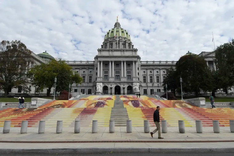 The Pennsylvania state Capitol, pictured above. The steps are covered with an art installation by Michelle Angela Ortiz showing images of young mothers who were held in a facility in Pennsylvania that is one of three family detention centers in the United States that holds children and parents who are seeking asylum or entered the country illegally. (AP Photo/Marc Levy)