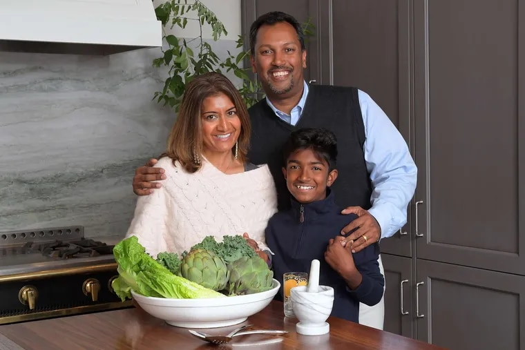 """Nazir Ali with his wife, Jyotika Vazirani, and their son, Tariq. Though most men prefer industrial-style ranges at home, Ali spends his workdays in an industrial-style commercial kitchen and wanted to emphasize their kitchen's homey feel. """"I wanted our kitchen at home to be a break from work,"""" Ali said."""