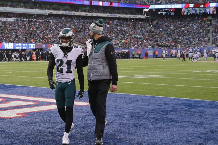 Eagles cornerback Patrick Robinson (left) leaves the field after suffering a concussion during Sunday's win at the New York Giants.