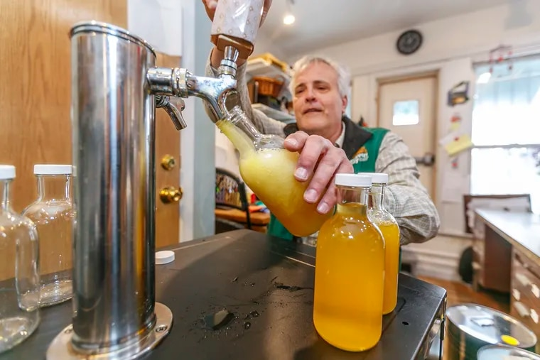 Weavers Way Co-op store manager Rick Spalek fills 16 ounce bottles with GT'S Cannabliss kombucha , which contains CBD, from the tap on the second floor of the Mount Airy store.