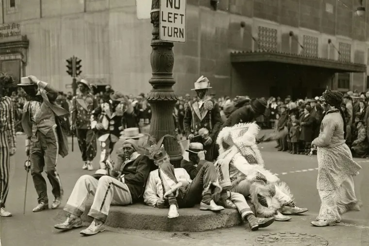 Mummers, including dudes in blackface, sit around the pole of a street sign during the parade in 1946.