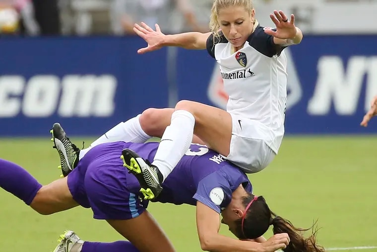 FILE - In this June 30, 2018, file photo, North Carolina Courage's McCall Zerboni, top, falls on Orlando Pride's Alex Morgan during an NWSL soccer game in Orlando, Fla. Zerboni is so dedicated to her soccer career that she once hawked random products to beachgoers in Southern California to make ends meet. Now 32, the savvy midfielder is getting her shot at the U.S. national team _ and a chance to make the roster for the World Cup this summer. She was named this week to the 23-player roster for the upcoming SheBelieves Cup tournament that kicks off Wednesday in Chester, Pennsylvania.(Stephen M. Dowell/Orlando Sentinel via AP, File)