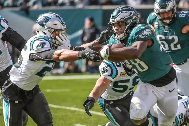 Wendell Smallwood stiff-arms Panthers' safety Eric Reid in the second quarter of Sunday's loss.