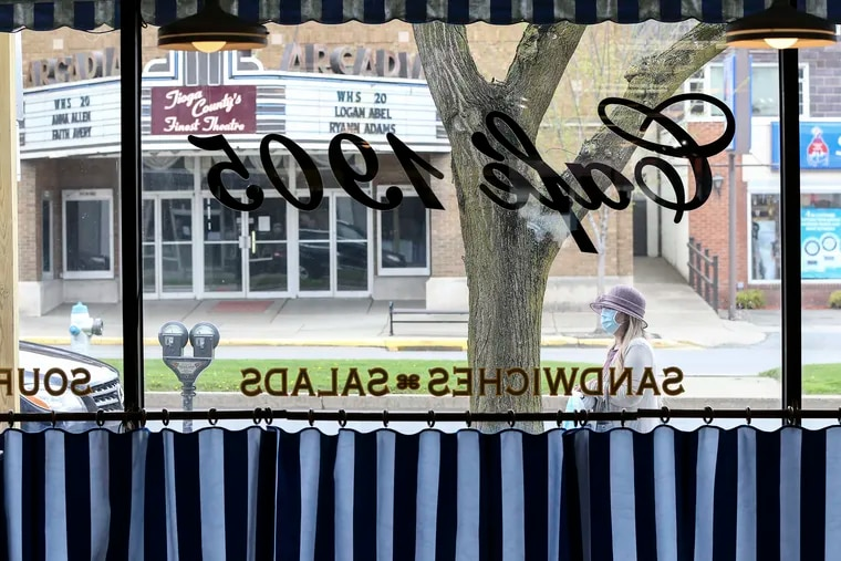 Looking through the window of the Cafe 1905, a sandwich and coffee shop in Dunham's Department Store in Wellsboro, Tioga County, where many businesses were allowed to reopen on Friday. The still-closed movie theater across the street displays names of the 110 graduating students of Wellsboro High School, changing the names daily.
