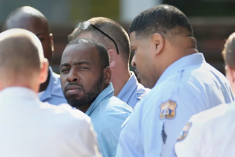 Maurice Hill, accused of shooting six police officers during an hours-long standoff, is led out of the Philadelphia Police Department 1st District station in South Philadelphia after being arraigned in August. Hill surrendered after allegedly barricading himself in a Tioga home for hours and repeatedly firing on officers.