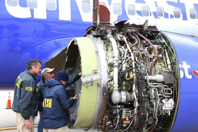 National Transportation Safety Board investigators examine damage to the engine of the Southwest Airlines plane that made an emergency landing at Philadelphia International Airport.