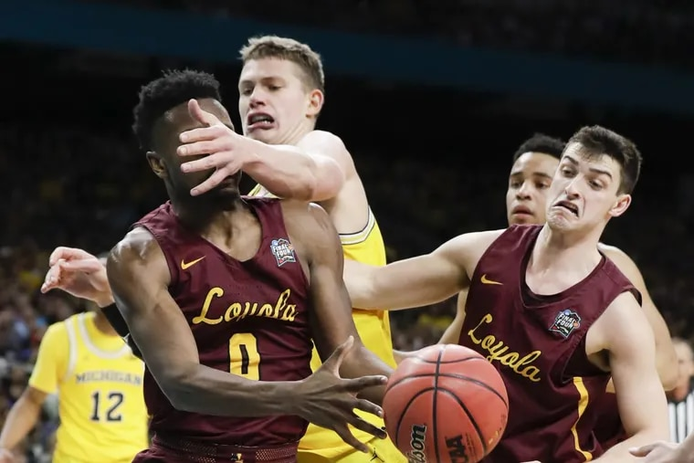 """Michigan forward Moritz """"Moe"""" Wagner (center) sticks his arm in front of guard/forward Donte Ingram (left) next to guard Clayton Custer during the first-half in the NCAA Basketball Tournament National semifinals game on Saturday, March 31, 2018 at the Alamodome in San Antonio."""