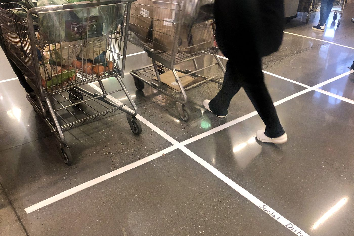 Tape on the floor reminds shoppers to stay six feet apart at the checkout counter.