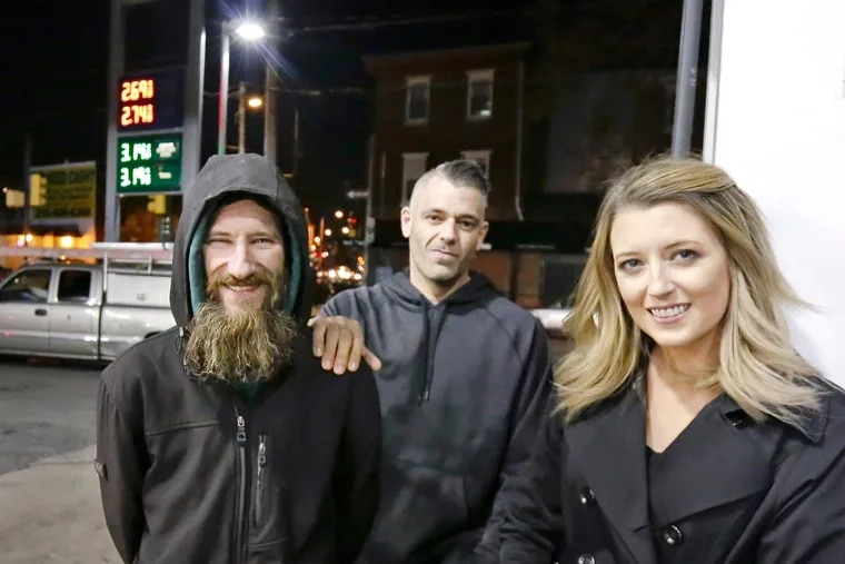 Johnny Bobbitt Jr., left, Kate McClure, right, and Mark D'Amico pose at a Citgo station were they claimed Bobbitt purchased gas for McClure's stranded car.
