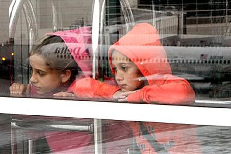 Two sisters watch airplanes at the Detroit airport before they boarded a flight to Florida on Sunday. (AP Photo / Charles Rex Arbogast)