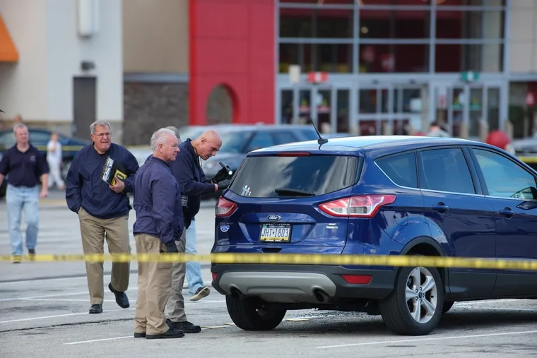 Springfield Township officers process the scene of Saturday's shooting in the Springfield Mall parking lot.