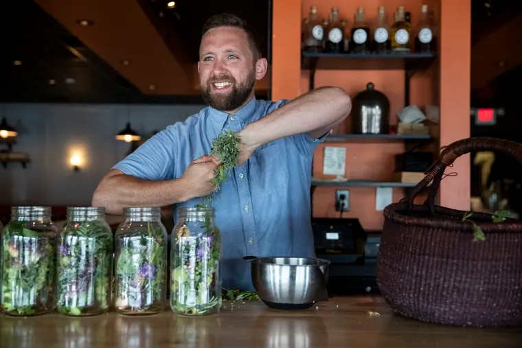 Danny Childs, bar manager at the Farm and Fisherman Tavern, fills jars with foraged botanicals in Cherry Hill, N.J., on Monday, July 12, 2021. Childs makes amari and other cocktails using foraged botanicals and plants from his garden.