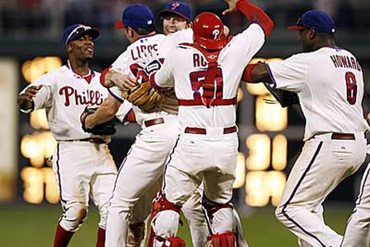 Brad Lidge is mobbed by teammates as they celebrate their NL East title. (Tom Mihalek / AP)