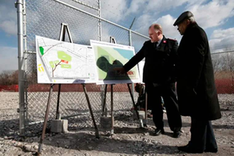 Maj. Paul Cain (left), of the Salvation Army, and Theodore Z. Davis, the city's state-appointed chief operating officer, examine plans for a community center on the landfill site.