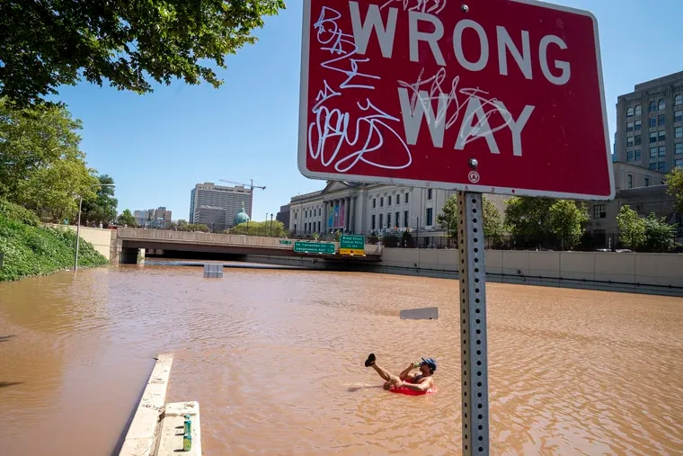 Austin Ferdock drinks a beer while floating in floodwater that continues to rise over the submerged Vine Street Expressway, Interstate 676, following a storm amid the remnants of Hurricane Ida, on September 2, 2021, in Philadelphia. (Jessica Kourkounis/Getty Images/TNS)
