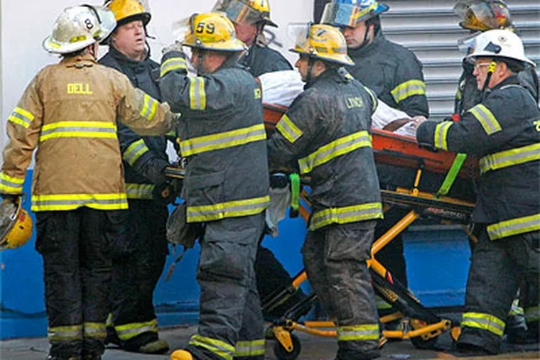 Holding the helmet of a fallen firefighter, a battalion chief (left) works along with rescue personnel to move the victim to a waiting medic unit at the fatal 5-alarm blaze in East Kensington. (Alejandro A. Alvarez / Staff Photographer)