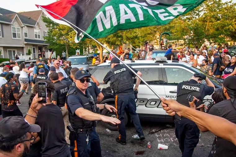 Edward Cagney Mathews is driven away in a police cruiser after he was escorted by police through a crowd of protesters on July 5.
