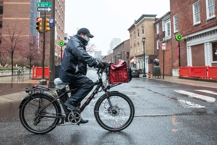 A masked food delivery bicycle rider makes his way south on 10th Street in a deserted Center City last week.