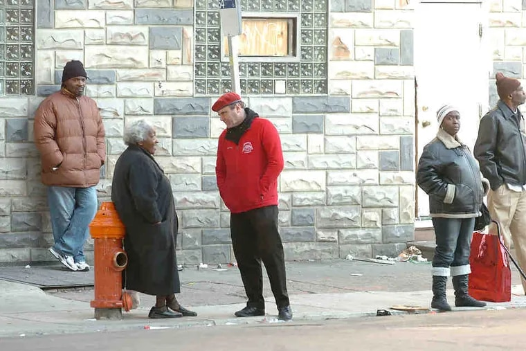 Guardian Angels' Curtis Sliwa (center) talks with Pat Thompson, waiting for a bus at Kensington Avenue and Somerset Street.