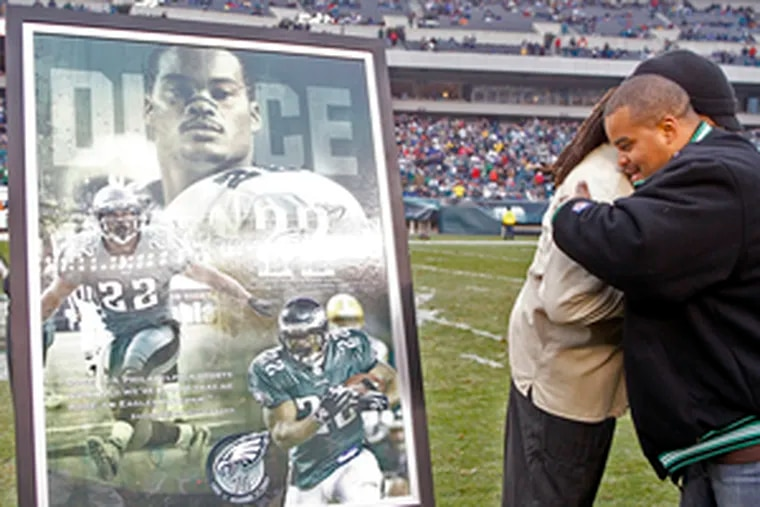 Duce Staley (right), attending his retirement ceremony at halftime, hugs former teammate Cecil Martin.