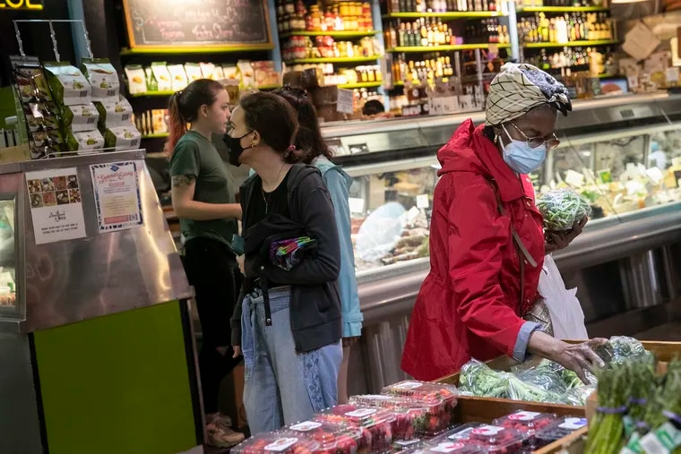 Beatrice Brown, 73, wears two masks while shopping for produce inside Reading Terminal Market on  June 11. The city is again recommending that everyone wear masks inside public places, regardless of vaccine status. Brown said she never stopped doing that.