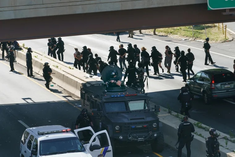 Police with protesters who were arrested after they descended onto I-676 and blocked traffic on June 01 amid protests over the killing of George Floyd by Minneapolis police.