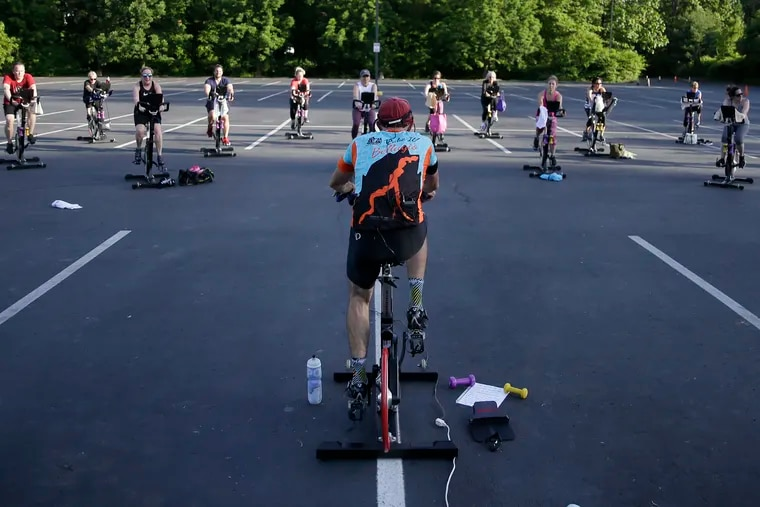 """Cycling instructor Tom Hambrose (foreground) leads the 45 minute """"Cycling with Tom"""" spin class in the parking lot at Royal Fitness in Barrington, N.J. on May 27, 2020."""