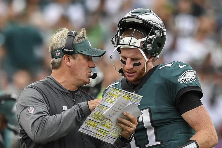 Eagles quarterback Carson Wentz and head coach Doug Pederson confer about a play against the Cardinals.