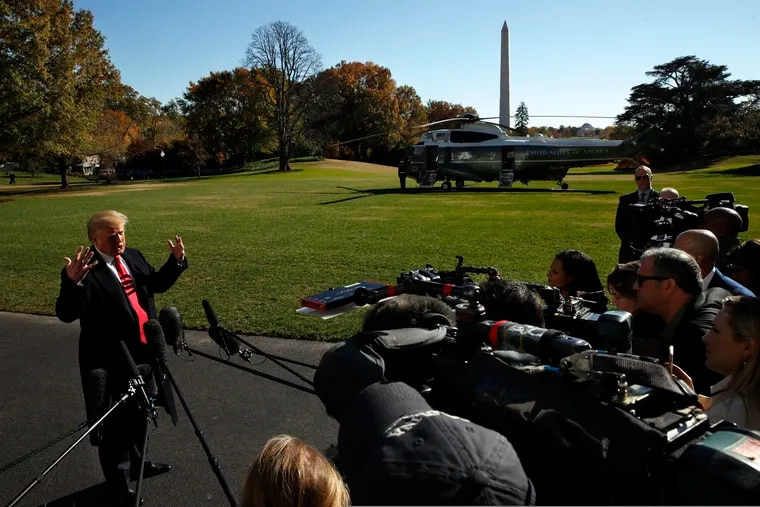 President Donald Trump answers questions from members of the media as he leaves the White House in 2018. His attacks on the media have hurt press freedom.