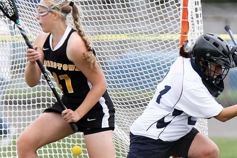Moorestown's Kayla Pruitt distracts the Shawnee goalie Lily Argyle enough to allow a shot by teammate Sydney Dalmass into the goal during the first half of girls field hockey in Medford, May 7, 2013. (David M Warren/Staff Photographer)
