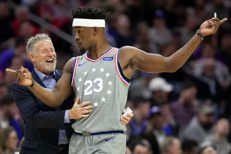 Sixers head coach Brett Brown laughs with Jimmy Butler during the third quarter against the Washington Wizards in Philadelphia on Nov. 30, 2018.