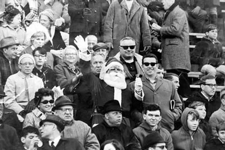Shown in this 1967 copy photograph is Eagles fan Frank Olivo, center, wearing his Santa suit in the stands of an Eagles game at Franklin Field in 1967. Olivo was the Santa who was booed and dodged snowballs during halftime at a 1968 Eagles game. (AP Photo)
