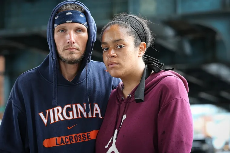 """Daniel Schroeder (left) and Ariana Kemecak, a homeless couple who have been living on the streets of Kensington since January, at Kensington Avenue and Tioga Street in Philadelphia. """"It's hard even without the virus to find a couple's shelter,"""" Schroeder said."""