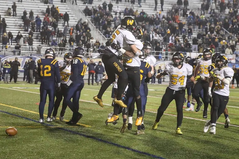 Wood's Ryan Woertz (5) hugs Cardel Pigford after Pigford scored the winning  touchdown.