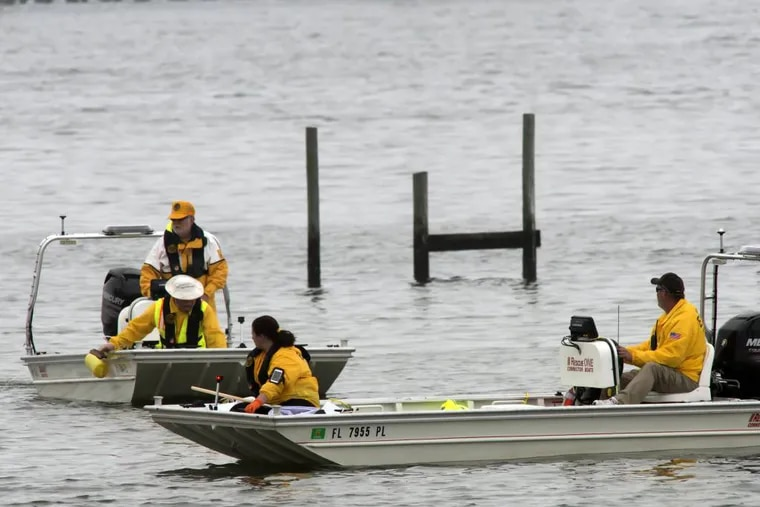 Military and civilian personnel search the waters Wednesday, March 11, 2015 in Navarre, Fla.  (AP Photo/The Pensacola News Journal, Tony Giberson)