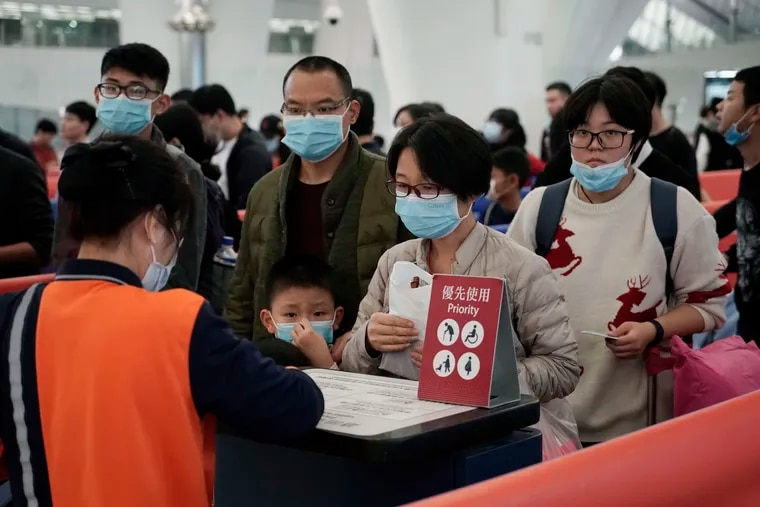 Passengers wear masks to prevent an outbreak of a new coronavirus in the high-speed train station in Hong Kong on Wednesday. The first case of coronavirus in Macao, in a woman who traveled from Wuhan, was confirmed on Wednesday, according to state broadcaster CCTV.