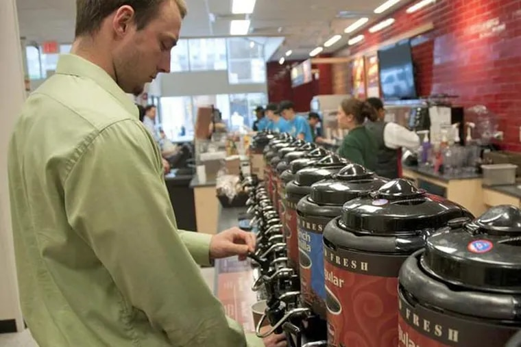 Brian Garraty of Glenolden  fills a cup with coffee at the expanded Wawa, which also hopes to attract residents moving into apartments above the store. ABI REIMOLD / Staff Photographer