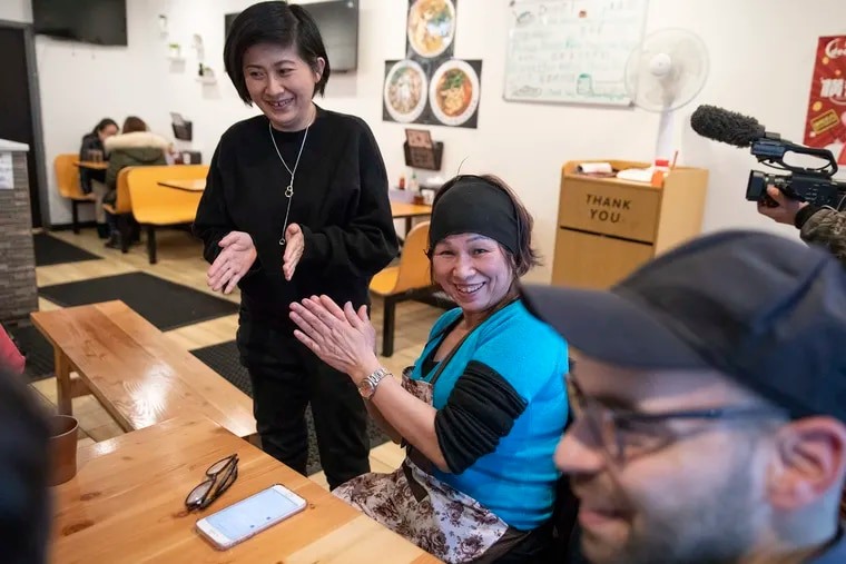 Lily Yau (center) claps along with Hong-Kai Wang (left) and Eric Laska after singing a Cantonese song at her restaurant, Hidden Gem, in Chinatown.